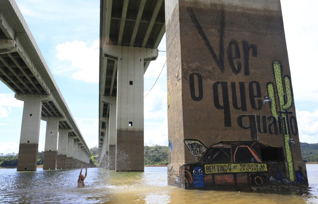Artist Thiago Mundano splashes the mural he painted on the legs of a bridge in the Cantareira reservoir. The mural lies where the 'Welcome to the Cantareira desert' car once stood. Photograph: Frederick Bernas